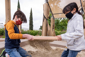 two kids sifting through dig pit