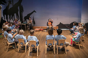 Group of children seated in chairs in a semi-circle around a guide at Noah's Ark exhibit