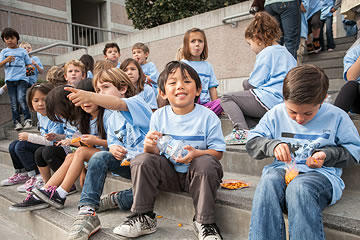 Children seated in amphitheater, eating a snack