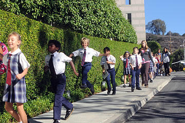 Children walking and skipping down the sidewalk in front of Skirball Cultural Center