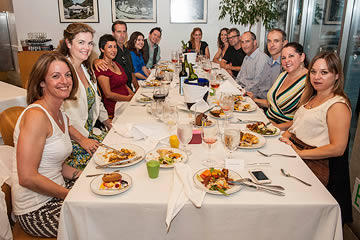 Group photo of people seated around a long dining table