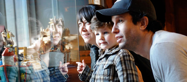 Family looking at a display, their reflection showing in the display glass