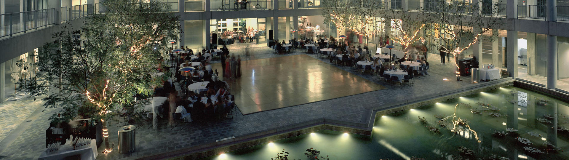 People sitting at tables in Taper Courtyard at night