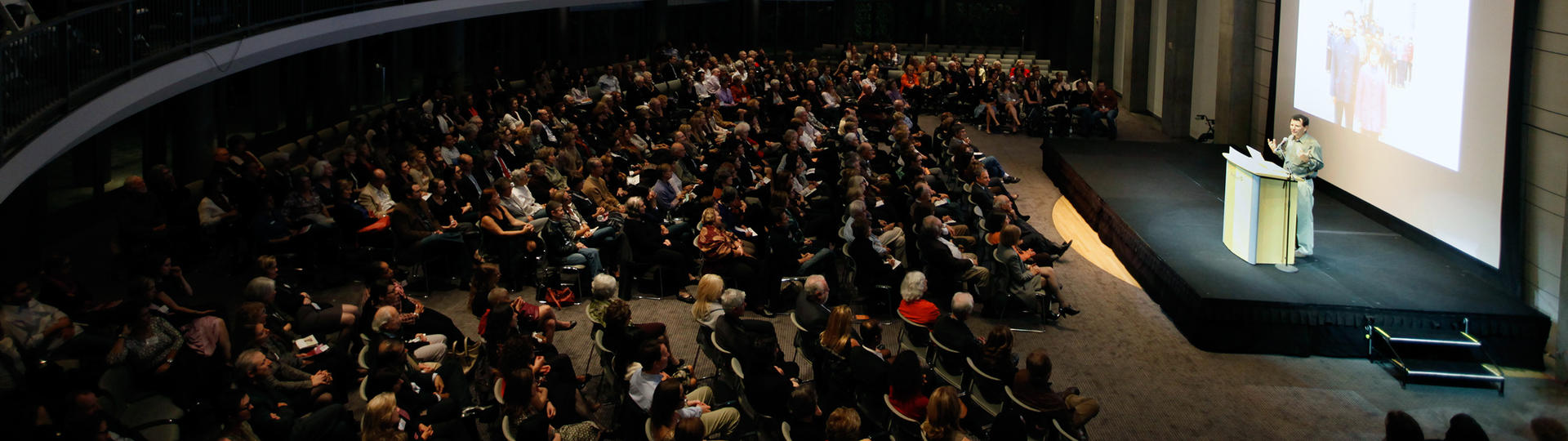 Lecturer on a stage talking to a large audience seated below