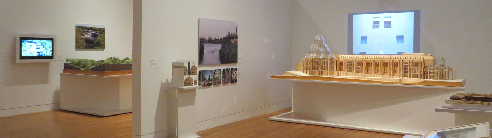 exhibition gallery displaying architectural models and images