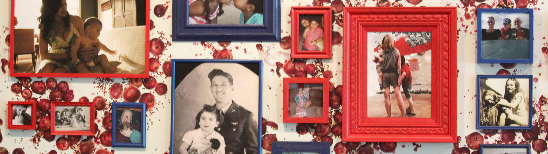 Various photographs of people framed in red and blue frames on a wall covered in wallpaper with a pattern of pomegranites
