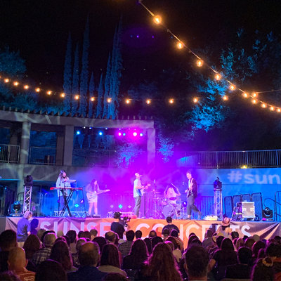 Skirball Taper Courtyard lit in shades of purple and blue with Run River North mid-performance on stage